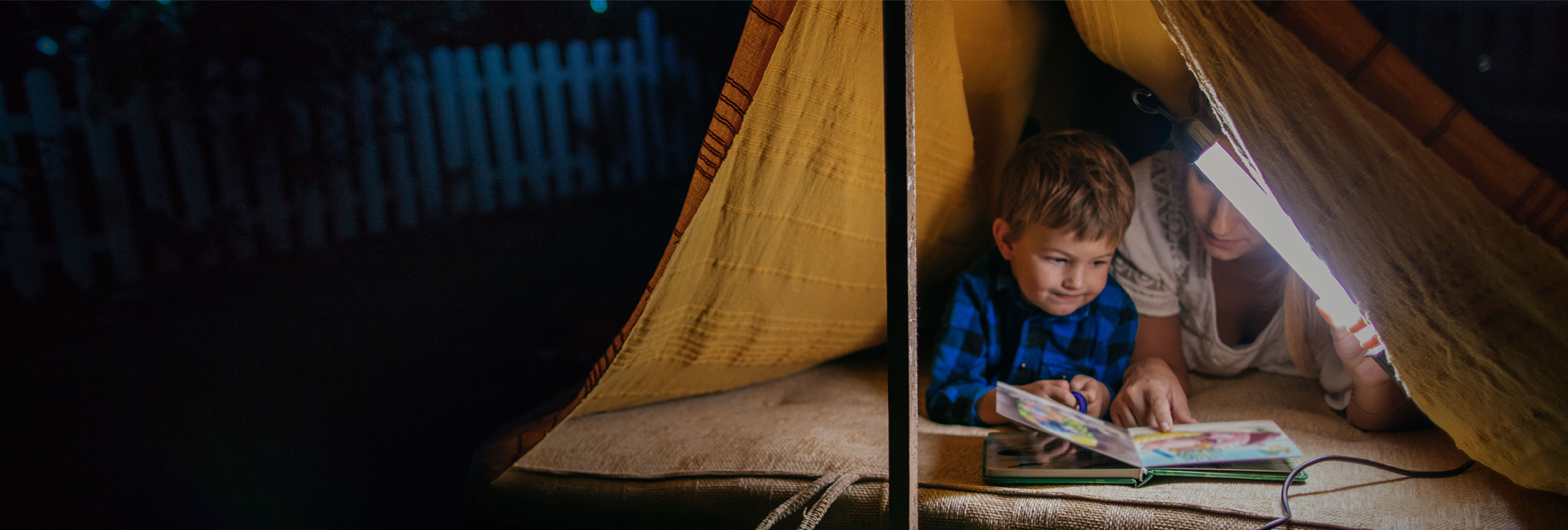 Little boy and mother in tent in backyard
