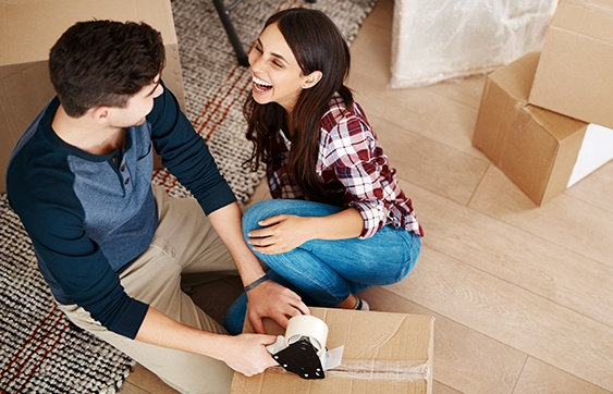Young couple taping up packing boxes