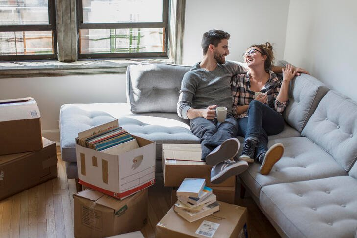 Woman laughing with man on grey couch with boxes packed around them